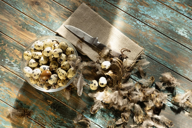 Ovos de codorna em uma tigela sobre um fundo azul de madeira decorado com penas, um guardanapo e uma faca