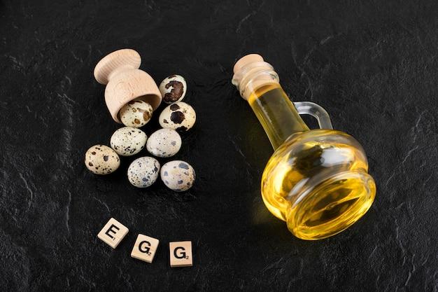 Ovos de codorna frescos de fazenda e azeite de oliva na superfície preta.