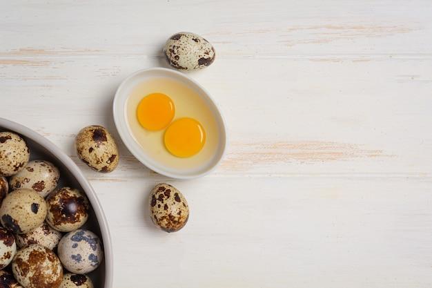 Ovos de codorna frescos na superfície de madeira branca.