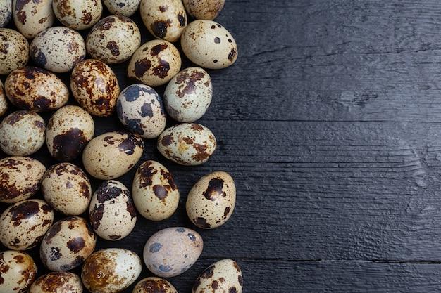 Ovos de codorna frescos na superfície de madeira escura.