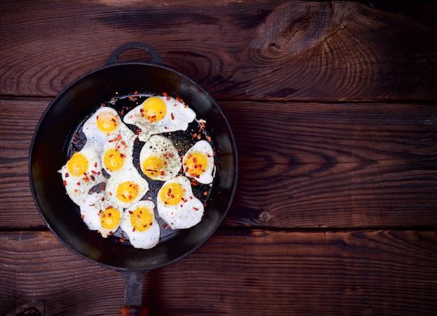 Ovos de codorna frito em uma frigideira de ferro fundido preto