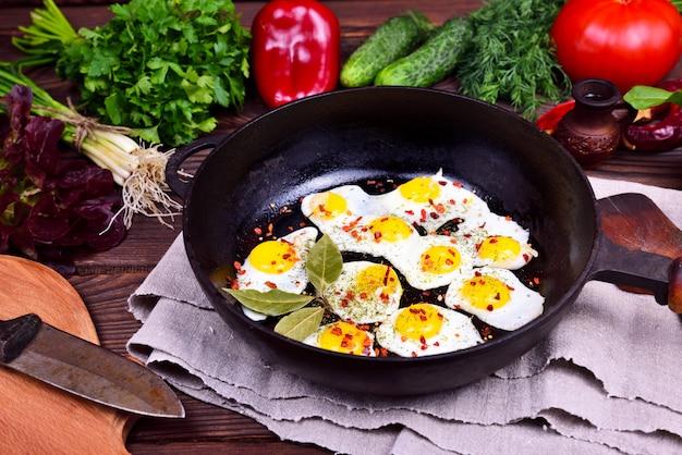 Ovos de codorna frito em uma frigideira de ferro fundido