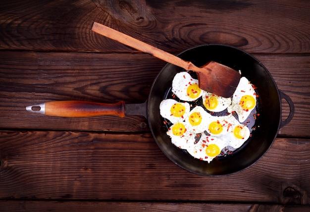 Ovos de codorna frito em uma frigideira preta