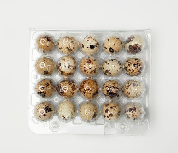 Ovos de codorna inteiros crus marrons em uma bandeja plástica, vista superior