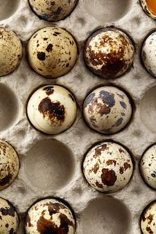 Ovos de codorna na embalagem de papelão na mesa cinza riscada
