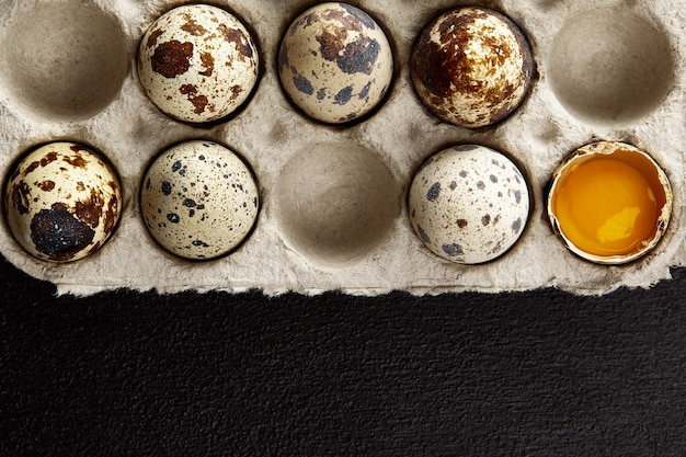 Ovos de codorna na embalagem de papelão na mesa cinza riscada.