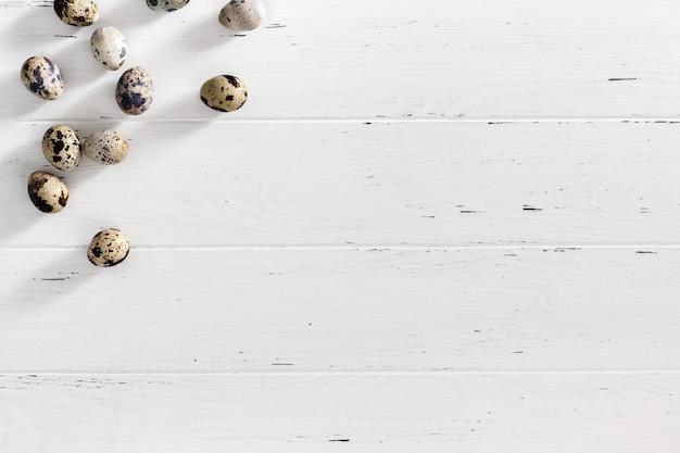 Ovos de codorna na superfície mínima de madeira branca