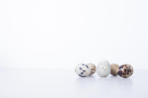 Ovos de codorna orgânicos na superfície branca.