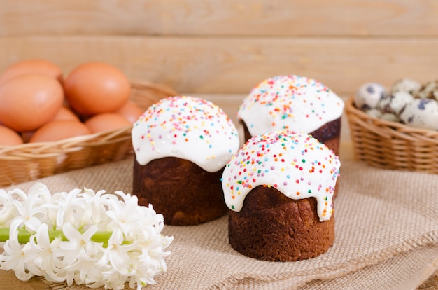 Ovos de codorna, ovos de galinha em uma cesta, bolo de páscoa em fundo de madeira rústica na serapilheira