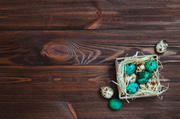 Ovos de codorna turquesa pintados sobre fundo de madeira