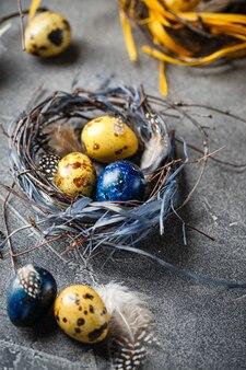 Ovos de codorniz da páscoa coloridos amarelos e azuis em pequenos ninhos. ovos de codorna para o feriado de páscoa católico e ortodoxo. profundidade superficial de campo.