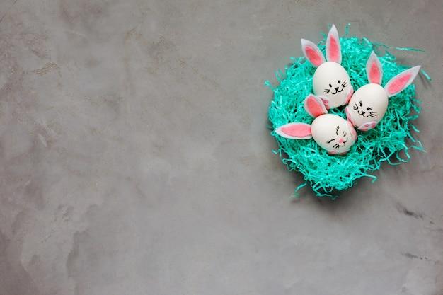 Ovos de coelhinhos da páscoa no ninho turquesa