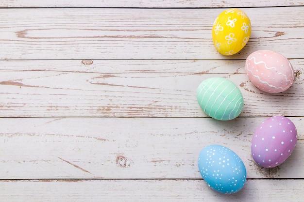 Ovos de cores pastel pintados à mão na mesa de madeira colorida luz.
