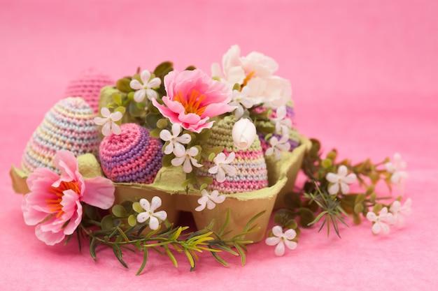 Ovos de decoração de páscoa de malha, flores sobre um fundo rosa, feitos à mão