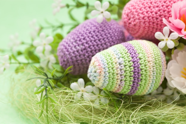 Ovos de decoração de páscoa de malha, flores sobre um fundo verde, feito à mão