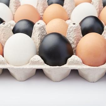 Ovos de diferentes cores em caixas de papelão. ovos de galinha pretos, brancos e marrons.