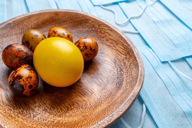 Ovos de éster na tigela de madeira em um fundo de máscaras médicas azuis