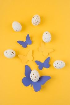 Ovos de galinha branca com borboletas de papel na mesa