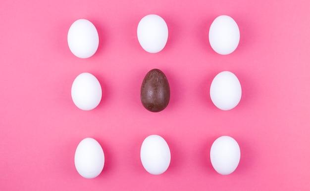 Ovos de galinha branca com ovo de chocolate na mesa