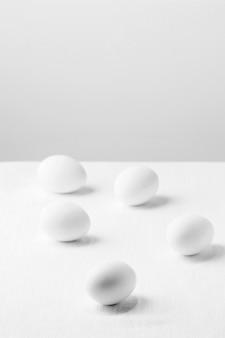 Ovos de galinha branca de ângulo alto na mesa com cópia-espaço