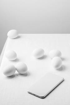 Ovos de galinha branca de ângulo alto na mesa com o telefone