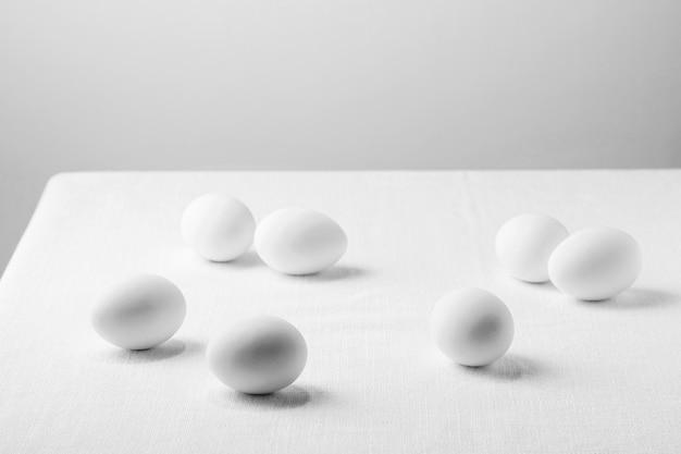 Ovos de galinha branca de ângulo alto na toalha de mesa