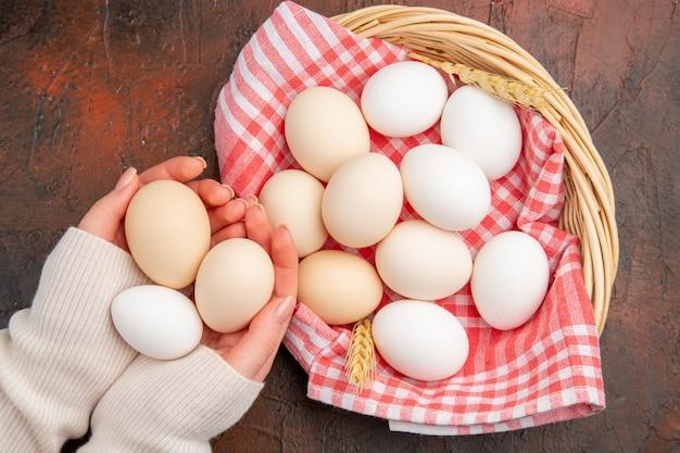 Ovos de galinha branca de vista superior dentro de uma cesta com uma toalha na mesa escura comida crua fazenda café da manhã foto colorida refeição