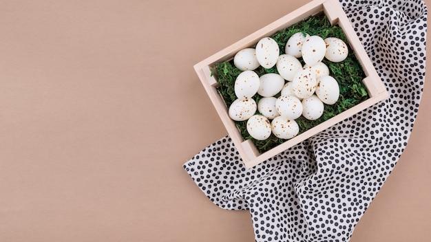 Ovos de galinha branca em caixa de madeira na mesa