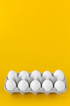 Ovos de galinha branca em caixa de papelão aberto em fundo amarelo