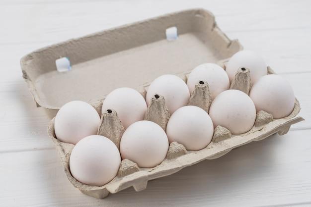 Ovos de galinha branca em rack na mesa de luz