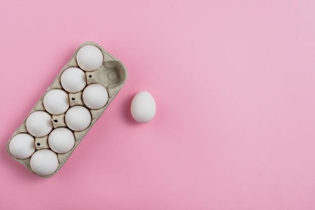 Ovos de galinha branca em rack na mesa-de-rosa
