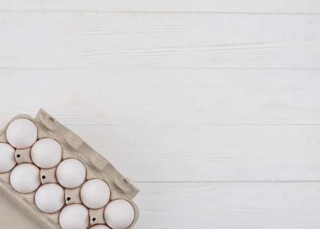 Ovos de galinha branca em rack na mesa