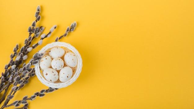 Ovos de galinha branca em tigela com ramos de salgueiro