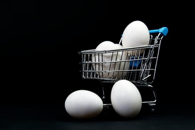 Ovos de galinha branca em um carrinho de compras.