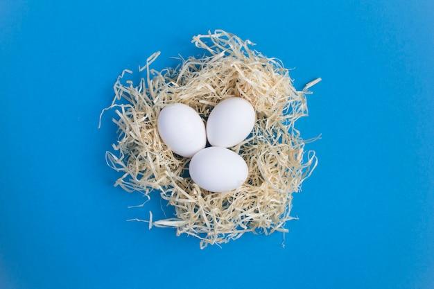 Ovos de galinha branca em um ninho de palha no fundo azul