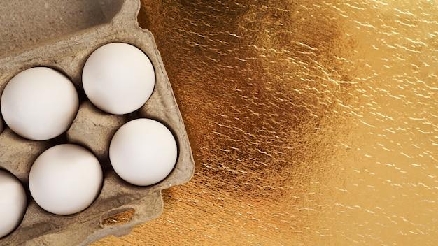 Ovos de galinha branca em uma bandeja de papelão em um fundo dourado. plano de fundo com lugar para texto. alimentos saudáveis e o conceito de páscoa. alimento proteico