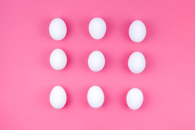Ovos de galinha branca espalhados na mesa-de-rosa