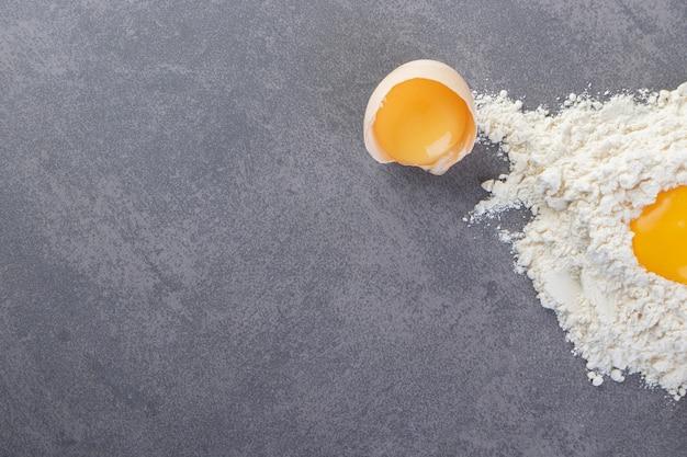 Ovos de galinha branca fresca crus colocados sobre uma mesa de pedra.