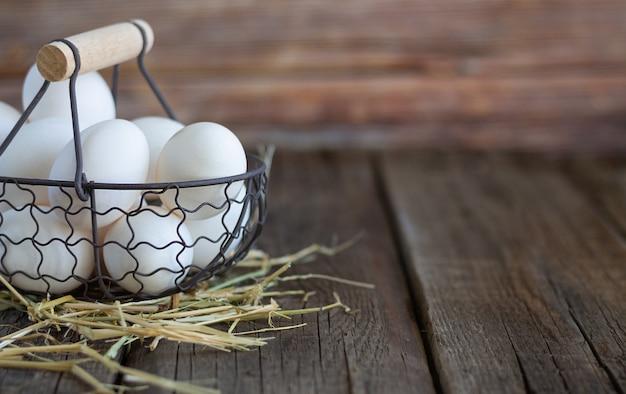 Ovos de galinha branca fresca na cesta em fundo rústico