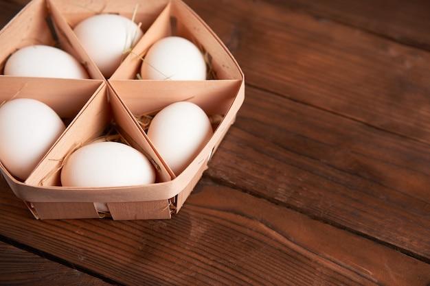 Ovos de galinha branca mentem em uma cesta de madeira redonda que fica sobre uma mesa de madeira escura.