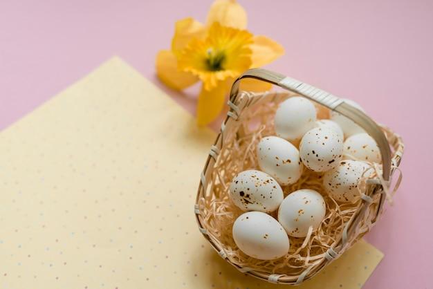 Ovos de galinha branca no cesto com flor