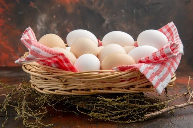 Ovos de galinha brancos de vista frontal dentro da cesta com uma toalha na superfície escura