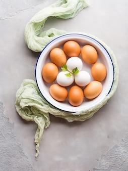 Ovos de galinha brancos e marrons na bacia no fundo cinzento concreto