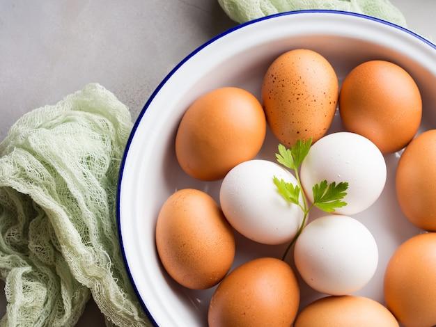 Ovos de galinha brancos e marrons na tigela em concreto cinza