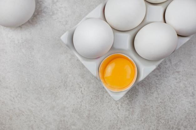 Ovos de galinha brancos em um suporte de cerâmica em uma superfície cinza claro