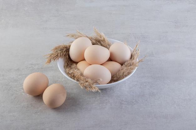 Ovos de galinha brancos frescos crus colocados sobre uma superfície de pedra.