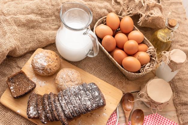 Ovos de galinha caseiros e pão acabado de cozer em uma mesa de madeira.
