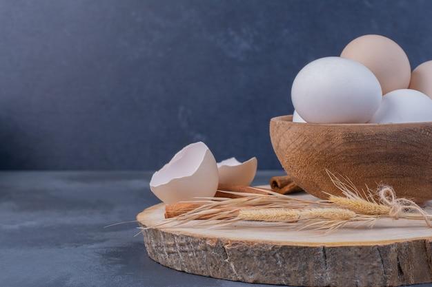 Ovos de galinha com cascas de ovo na travessa de madeira