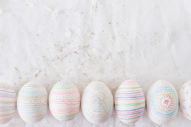 Ovos de galinha com padrões perto de penas em têxteis
