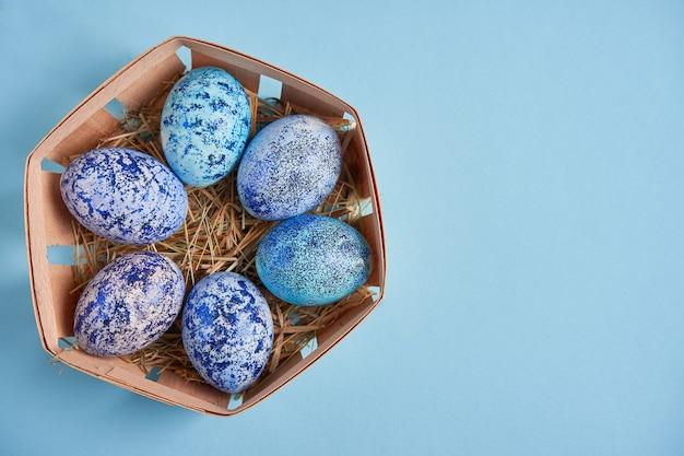 Ovos de galinha cosmos azuis repousam em uma cesta de madeira redonda que fica em uma superfície azul
